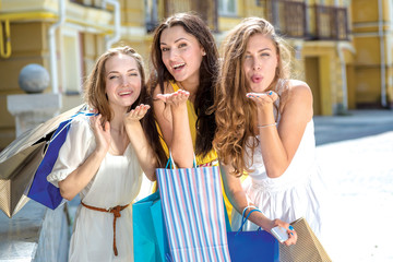 Kiss from three girlfriends. Three girls holding shopping bags a