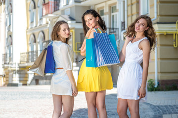 Joint purchases. Three girls holding shopping bags and walk arou