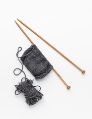 Piece of grey knitting on knitting needles