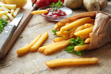 Fresh fries with ketchup on a table with knife