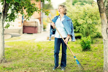 Mature woman raking leaves in her garden laughing.