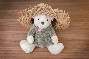 Toy teddy bear and hat on wooden background