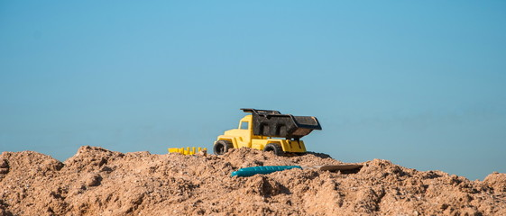 Small toy truck standing on a heap of sand