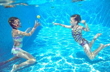 Happy kids swim in pool and play underwater having fun