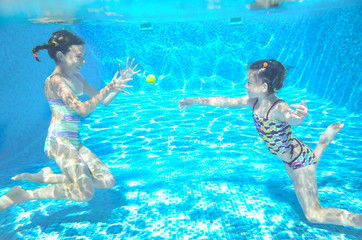 Happy kids swim in pool and play underwater having fun