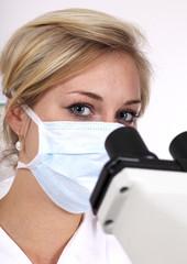 Wissenschaftlerin schaut ins Mikroskop in einer Labor