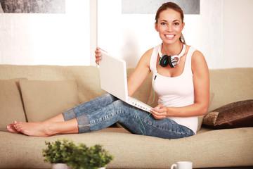 junge Frau mit Laptop auf Sofa