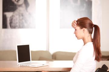 verzweifelte, junge Frau am Laptop