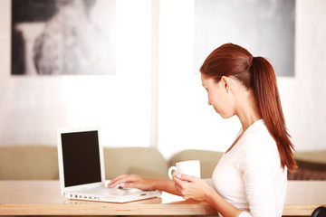 junge Frau am Laptop mit Kaffeetasse