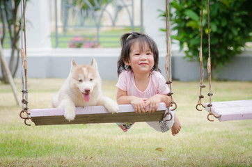 Asian baby  baby on swing with puppy