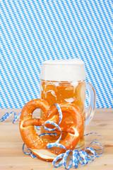 Eine Mass Bier mit Brezel vor Rautenhintergrund