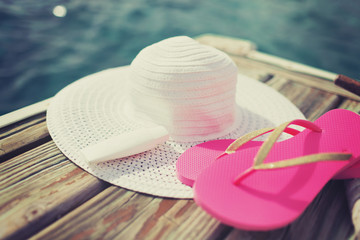 close up of hat, sunscreen and slippers at seaside