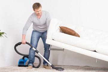 man does house work with vacuum cleaner.