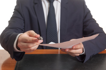 Businessman offering pen and documents for signing