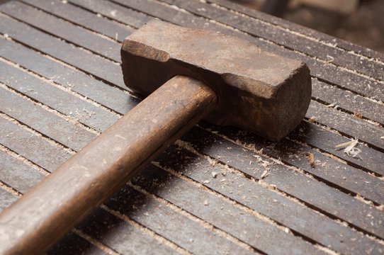 Big hammer on iron table with wooden dust.