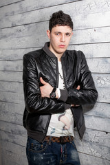 sexy brunette man in leather coat leaning against wooden wall