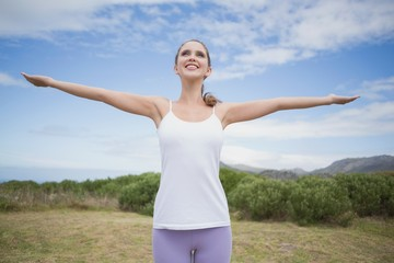 Woman standing with arms raised on countryside landscape