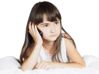 Caucasian child kid girl lying on bed with mobile phone isolated