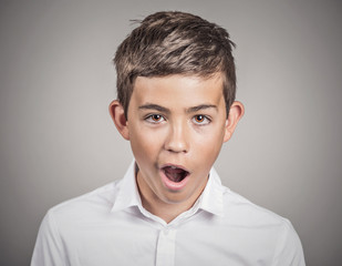 Boy shocked surprised in disbelief, grey wall background