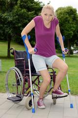 Frau erhebt sich an Krücken aus Rollstuhl