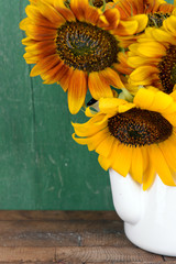 Beautiful sunflowers in pitcher on table on wooden background