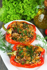 Stuffed red peppers with greens on plate on table close up