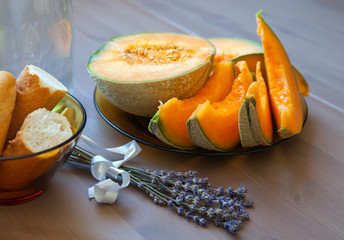Pieces of baguette and melon and lavender bunch on wood table