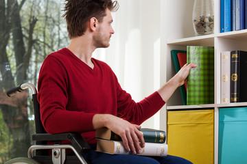 Disabled man cleanig up a bookshelf