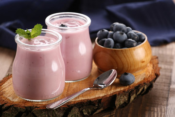 yogurt with blueberries in a glass jar and blueberries in a wood