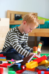 Boy playing with colored bricks