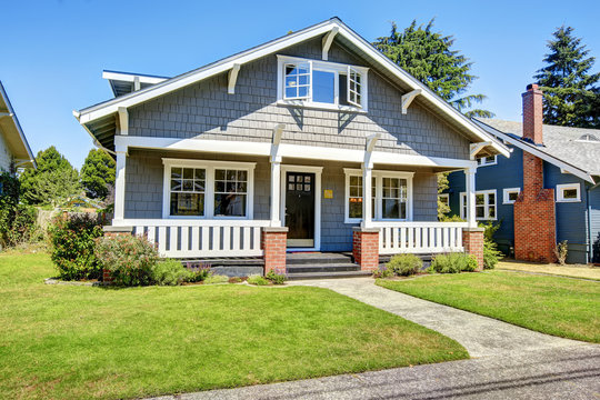 Clapboard siding house exterior. Large entance porch with brick