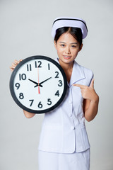 Asian young nurse point to a clock