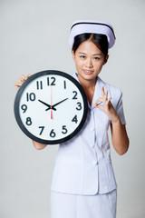 Asian young nurse show OK with a clock