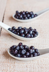 Blueberries in ceramic spoons, vertically