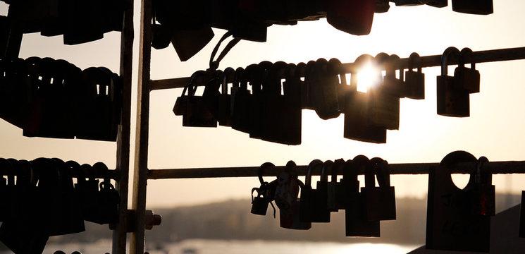 silhouette of padlocks against the sun