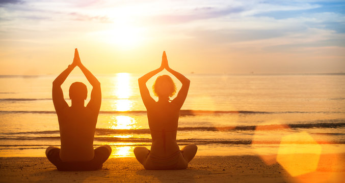 Yoga silhouette of a young couple on the beach at sunset.