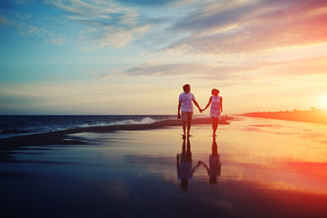 Happy romantic couple walking and holding hands on a beach