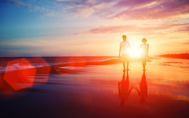 Beautiful young couple walking on a tropical beach at sunset,