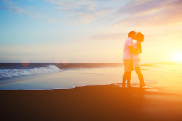Romantic couple kissing on the beach at colorful sunrise