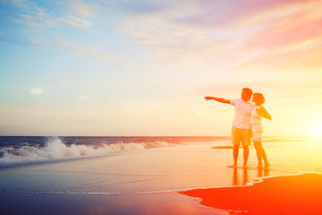 Happy young couple embracing enjoying ocean sunset
