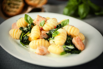 Italian gnocchi pasta with salmon and fresh basil
