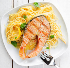 Healthy grilled salmon steak on linguine