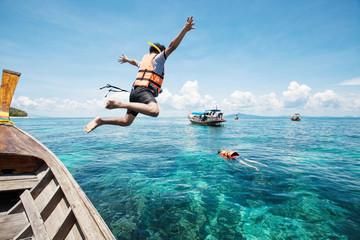 Fototapeta Snorkeling divers jump in the water obraz