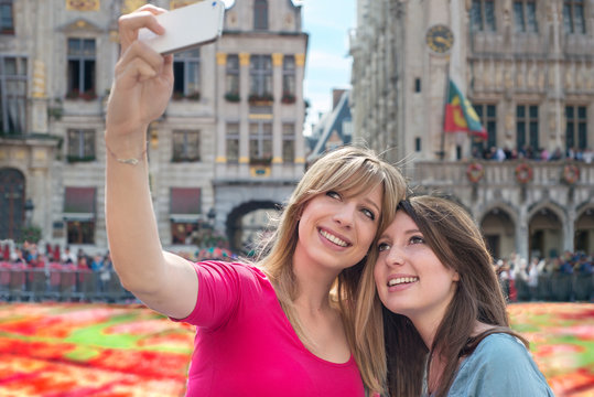 women taking a self portrait with smartphone against flower carp