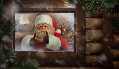 Santa Claus thumbs up through workshop window