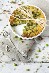 rustic vegetables quiche with peas on baking dish with fork