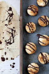 coconut macaroons with dripped chocolate on greaseproof paper