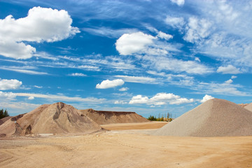 Sand and gravel quarry construction site with cloudy blue sky Wall mural