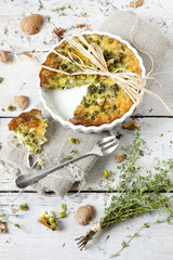quiche with peas and walnuts on baking dish with thyme bouquet