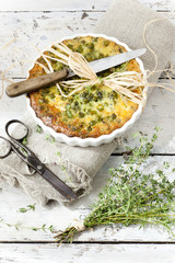 rustic french quiche with peas with thyme bouquet and scissor